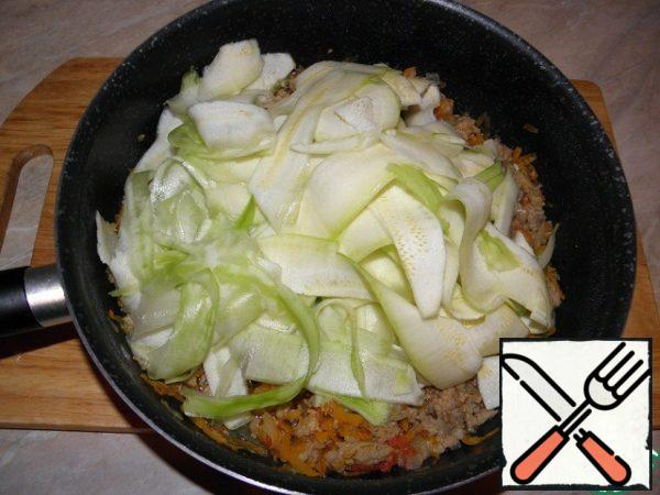 Spread the chopped zucchini to the minced meat in the pan, carefully mix them in the sauce for even distribution. We have only 5-7 minutes left to simmer zucchini.