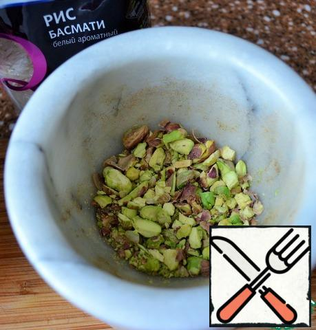 Pistachios grind in a mortar, lightly.