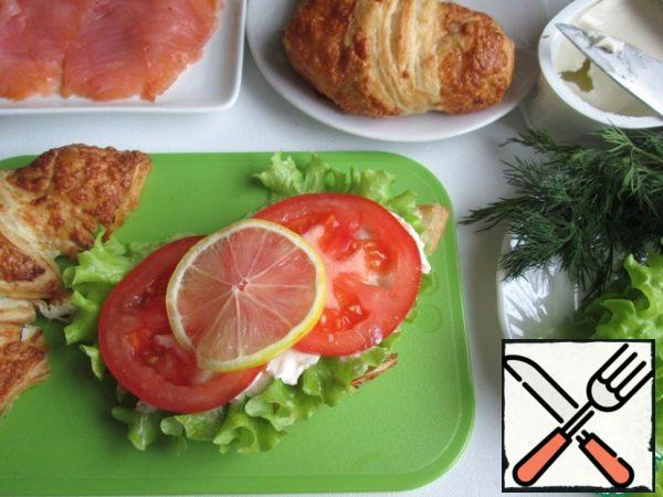Cut croissants in half lengthways. On the lower halves put lettuce and generously lubricate with cream cheese (or other, to taste). Then put slices of tomato and a slice of lemon.