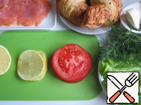 Croissants are ready, without filling. Lightly salted fish cut into thin slices. There's a ready-to-store cut. Tomato cut into thin slices. Lettuce and dill wash and dry. At will it is possible to take other greens. Lemon wash (can be pour boiling water), cut in half. We'll need half a lemon. From her cut 4 thin slices from the rest, squeeze the juice and sprinkle it over the fish.