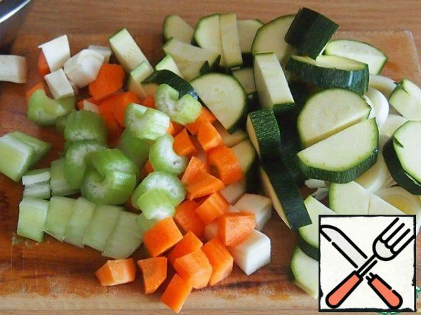 A small carrot, zucchini, and a sprig of celery cut into pieces. The white part of leek-rings.