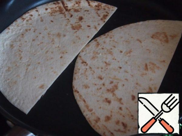 The meat is ready, cook the tortilla. Cut it into two halves and put on a hot dry pan. It is better to use a grill pan for a beautiful picture, but it does not matter. Heat the cake on both sides just a few seconds to make the cake warm and flexible. The main thing is not to dry the tortilla.