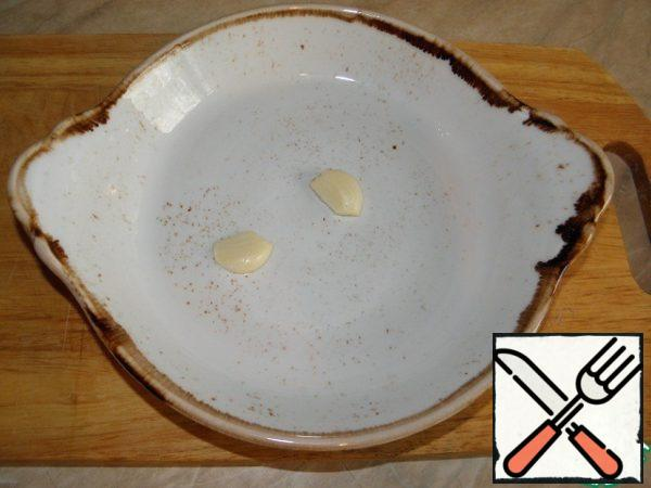 Slice garlic cut in half and RUB it into a baking dish. (the mold is better to use ceramic or cast iron)