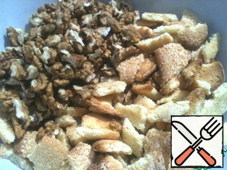 Chop cookies into not very small pieces. Prepare the nuts. Grind the kernels into halves or quarters.