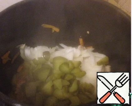 Fry the meat for 10 minutes, then add the bell pepper, onion and pickles, fry for 3 minutes.