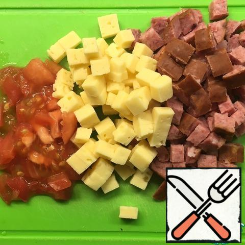 Cut the filling into cubes: sausage, cheese, tomato.
