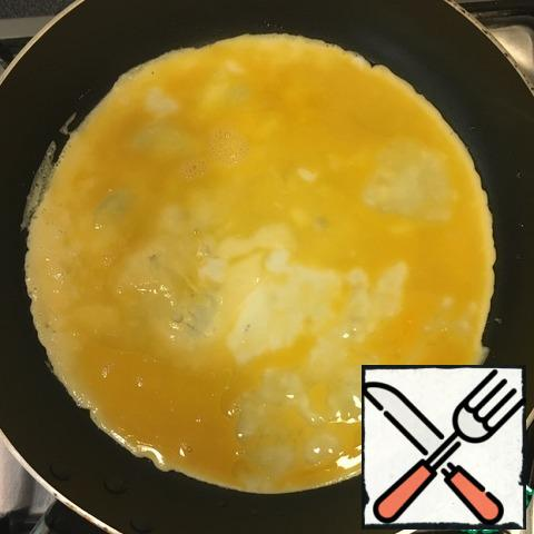 On a heated pan pour a little vegetable oil. Pour the egg mixture, distribute evenly.