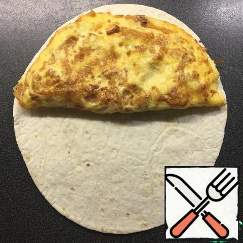 Spread the omelette on the tortilla, fold in half.