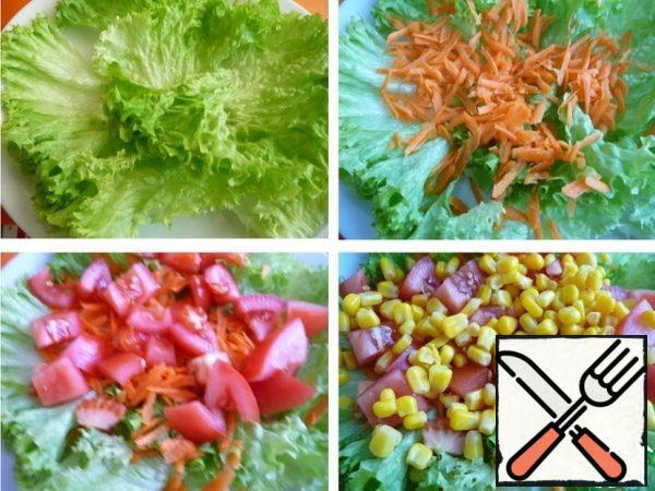 Lettuce wash, dry, pick hands. On a plate put lettuce. Grate the carrots. Tomato cut into cubes, put on top of carrots. Add corn.