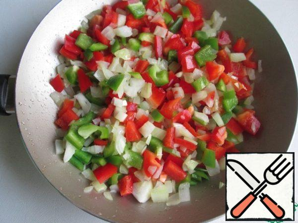 Add vegetable oil to the pan and put the onion. Through 3 minutes add green and red pepper. Stir and fry for 3-5 minutes.