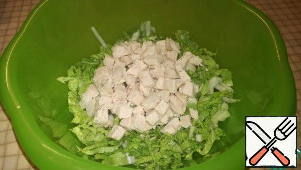 Cut thinly Peking cabbage. Pour into bowl. Boiled chicken fillet cut into cubes and send to the Beijing cabbage.