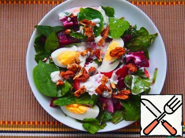 In a bowl lay the lettuce, top with sauce, put on top a few slices with eggs and sprinkle top with nuts.