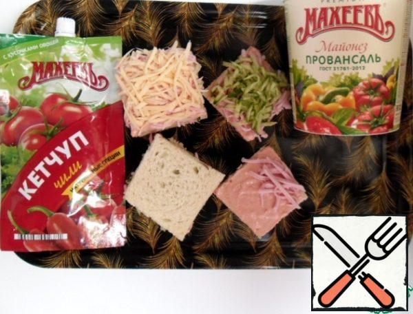 Combine mayonnaise with ketchup. Each layer of bread smear the resulting sauce. On the bottom put the sausage, then cucumber, lightly compacted. cover with a new layer of bread. Sprinkle with sausage, cheese on top. If You need to serve sandwiches, gently tamp the top, sprinkle coconut shavings. Coconut shavings, like all nuts, give the dish a taste, make it unique.