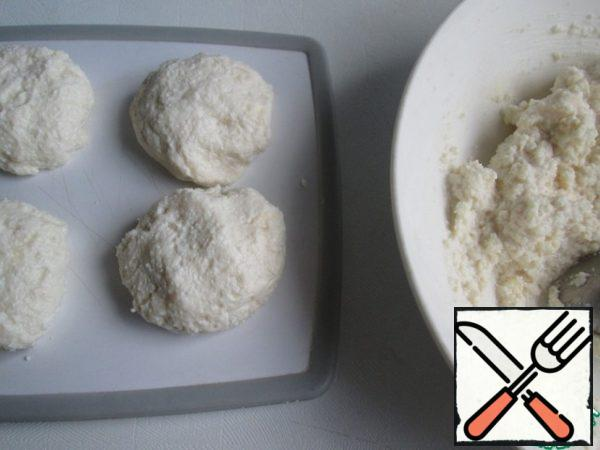 Then shape the cheesecakes: take a tablespoon of dough, roll it in your hands and a little crush. If the mass is soft and does not hold the shape, then add the flour to the dough and mix well. I added 1 tbsp flour, that was enough.