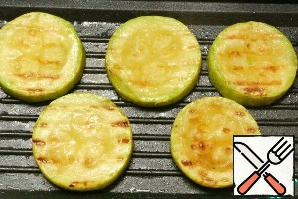 Fry in a pan-grill in vegetable oil on both sides of the zucchini circles. Salt is not necessary, as the salt will be in the sauce.
