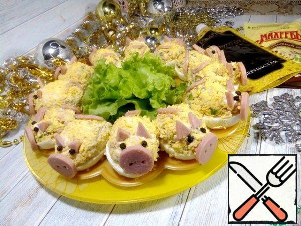"From the resulting salad to make balls, a little more walnut, roll in grated yolks and put in halves of proteins. Then arrange pieces of sausage in transforming ""pigs"". That's how cute they turned out."