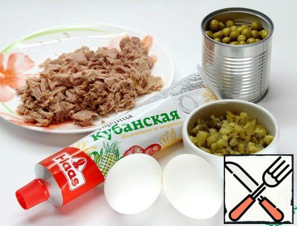 Everything is simple. Drain the juice from a can of tuna. Cut tuna, eggs and pickled cucumber into small cubes. Add two tablespoons of green peas.
