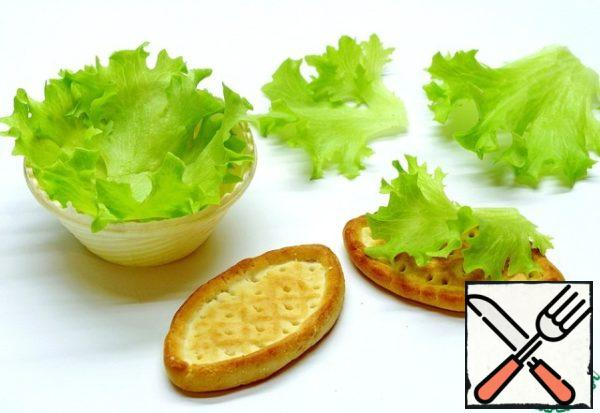 To tartlets or crackers are not quickly soaked under the influence of the sauce on the tartlets need to put lettuce. They will serve as a decoration and at the same time protect from getting wet.
