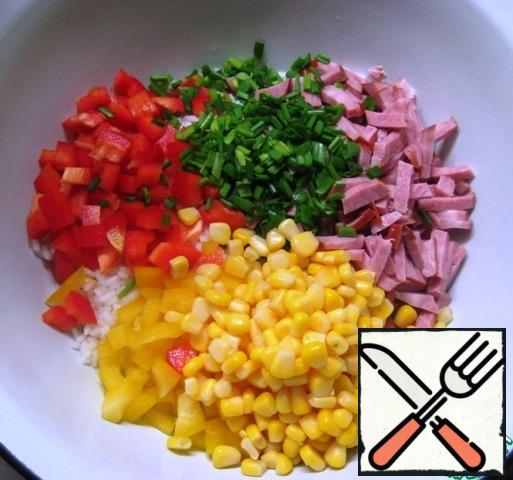 In a bowl, combine the pre-boiled and cooled rice, cut into small pieces of ham.