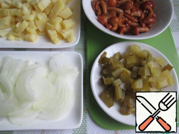 Dice the potatoes and pickles. Optionally, you can take two cucumbers. Onions cut into thin feathers. To get from the banks marinated mushrooms and drain off liquid.