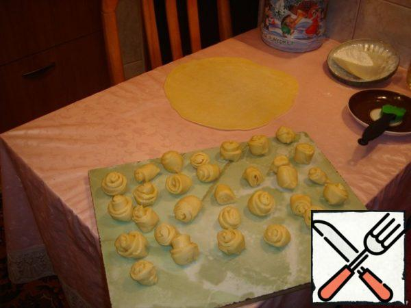 "Roll out the dough in a large circle, thickness = 2 mm, grease with vegetable oil and roll into a roll. Cut into pieces and sculpt ""roses"". Transfer to a large pot for the volume of onions with chicken, top with the sliced potatoes and then the ""roses"" of the test."