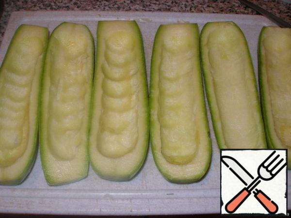 Prepare zucchini: wash, cut along, gently remove the pulp with a teaspoon (without damaging the edges and bottom).