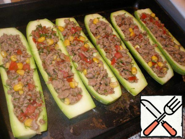 Mix the ready minced meat with vegetables and fill the prepared zucchini with this mixture.
