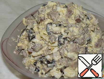 Grate the eggs. Mix tongue, prunes and eggs. Salad season with mayonnaise and put in a salad bowl.