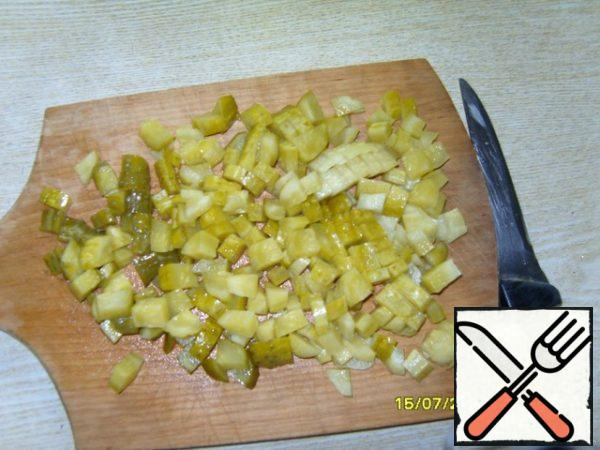 Cut pickled cucumbers and also spread to the peas and onions.