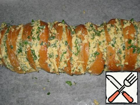 Cheese to grate, squeeze the garlic, add soft butter and finely chopped herbs, mix everything. Heat oven to 200 * C. In the loaf to make cuts obliquely, not cutting to the end, fill them well with cheese filling.