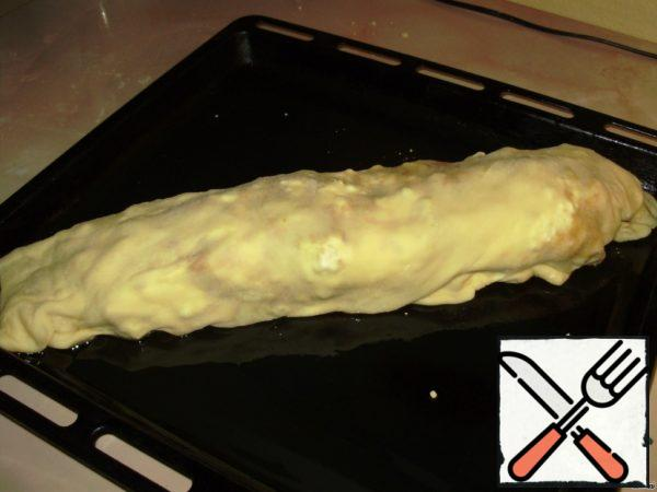 Grease a baking sheet with oil, put the strudel on top of the grease with butter. Bake for 30 min, a temperature of 220 C.