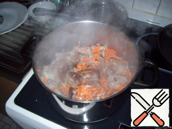 To the fried meat add medium cut (can be semi-rings) onions and carrots, cut into strips or grated on a coarse grater, fry everything a little.