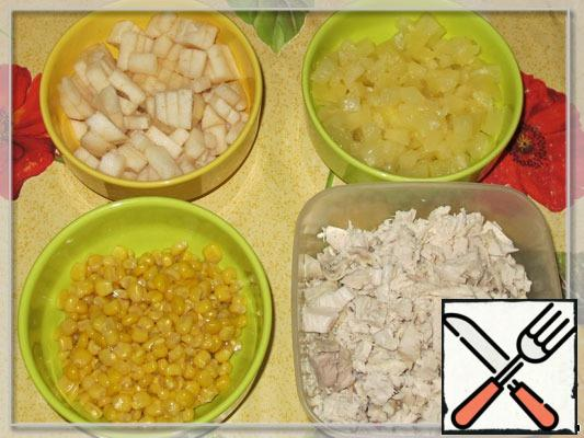 Chicken finely cut, pear clean, cut into small pieces. Drain the corn. Pineapple is also drained, finely cut, like a pear. The rice boiled and cooled.