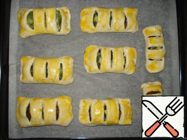 Place the layered strudels on a baking sheet covered with parchment paper in advance. Grease them on top of the yolk. Heat oven to 220 degrees (about 5 minutes). Put a baking sheet with strudels in the oven and bake for about 15-20 minutes until the strudels get a Golden color.