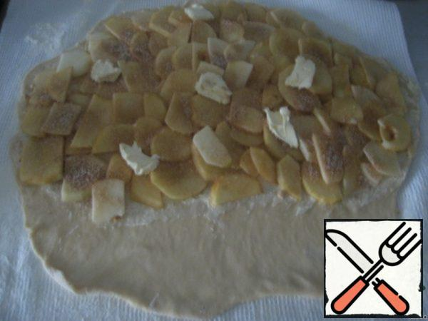 The dough is spread with butter and sprinkle with the breadcrumbs, leaving with the edge strip width of 10 cm evenly spread the apples, mix cinnamon with sugar and sprinkle the apples. For apples put a few pieces of butter. Use a towel to roll the roll .