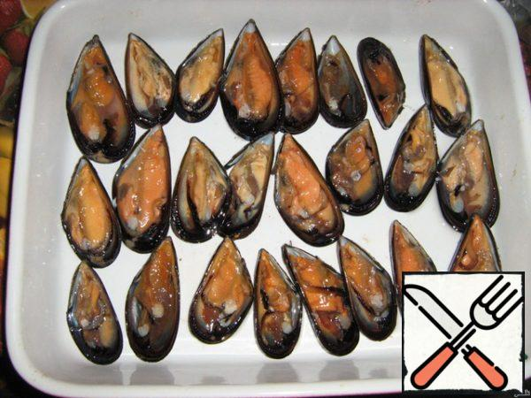 Mussels are cleaned of beard and well washed in cold running water. Open the shells and halves with clam stacked on a baking sheet.