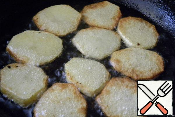 Potatoes cut into slices and fry on both sides in oil.