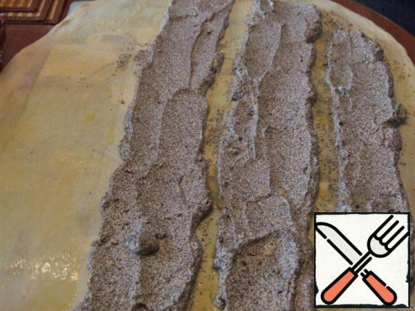 Spread the dough on the table (I have a flexible substrate on the table for the dough) and spread the filling along the long edge in three rows at a distance of 2-3 cm; the dough between the rows of the filling and the rest of the dough smear with melted butter.