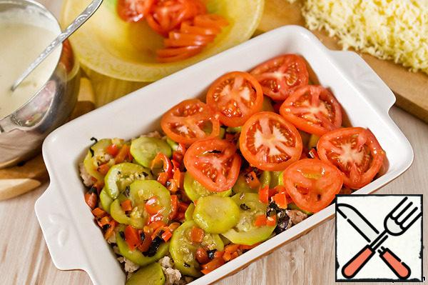 In the baking dish put the minced meat, then fried vegetables. On top lay the sliced tomatoes.