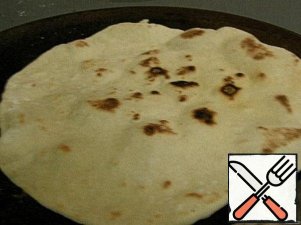 Put the tortilla on a heated pan and cook until the air bubbles. Turn over to the other side. Each side is cooked for about 30 seconds. Press on top of a wide blade to the center of the tortilla is also well roasted. And so we repeat with each tortilla. That's how they turn out. Ready tortillas are covered with a towel so as not to dry. When cool, put in a bag and in the refrigerator. They can be stored in the refrigerator for several days.