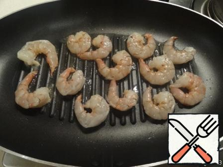Fry the shrimp in a hot pan with olive oil on both sides.