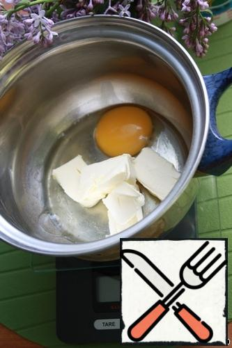 Then knead the dough: in a separate bowl / pan you need to put one egg, 50 grams of butter.