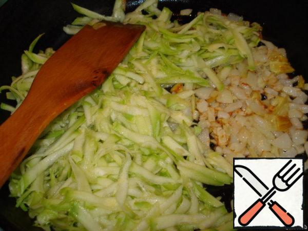 Add half of the grated zucchini (squeeze the juice) to the onions and fry on the heat for 2-3 minutes.