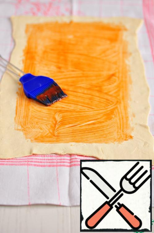 Thawed puff pastry roll out into a rectangle of size 25cm. 35 cm. Gently transfer the dough to a clean kitchen cloth. Brush to lubricate the surface of the dough with tomato sauce (ketchup).