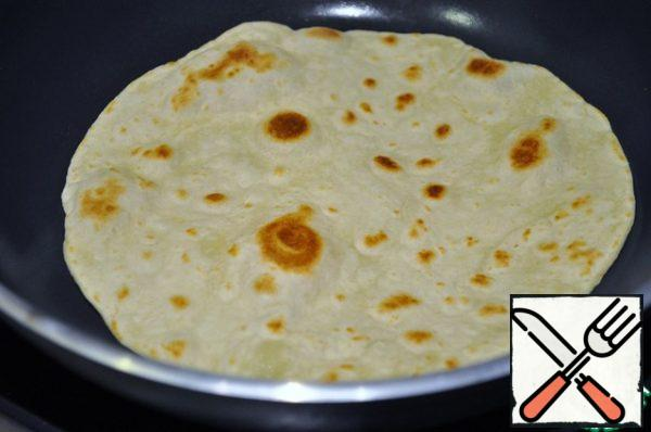 Take a dry pan with a thick bottom, heat it not very much and fry each tortilla for 2 minutes on each side.
