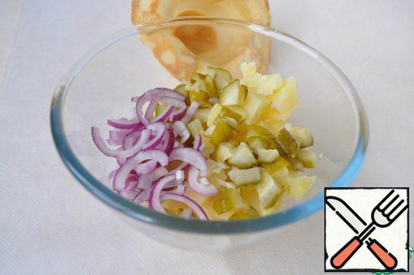 Cut potatoes, cucumber and onion for salad.