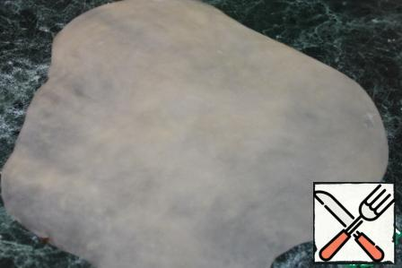 The table can not be floured, the dough will not stick. Roll out the dough as thin as possible, if you look closely, the photo shows how the pattern of the table top is illuminated.