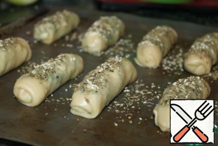 Spread the strudel on a baking sheet, covered with paper or silicone Mat, quite a bit on top of the grease with vegetable oil with a brush and sprinkle with herbs and sesame seeds Provencal. Send in a preheated 180*C oven for 30 minutes, but be guided by your plate, bake until light blush.