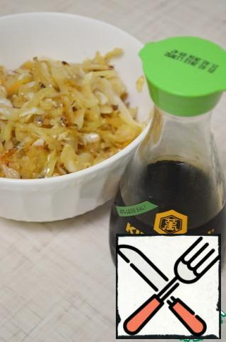 Heat oil in a frying pan. Onions chop, fry until transparent, then add the cabbage and fry. Add soy sauce, sugar, pepper to taste.