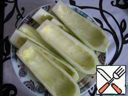 Zucchini clean, wash and remove the core with a teaspoon, get these boats that are a little prisalivaem to let the juice.